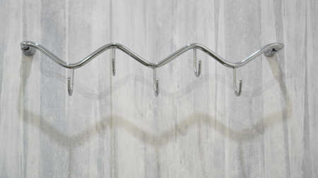 Metal adhesive hooks on gray background. Towel hangers