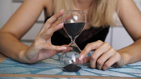 Male holds hourglass with black sand in hand 스톡 콘텐츠