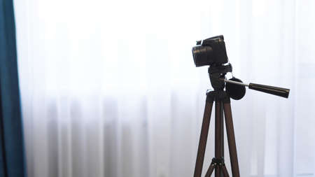 Camera on a tripod indoors. Filming a video blog or photographing at home - no visible brands. Stock fotó
