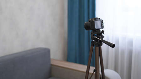Camera on a tripod indoors. Filming a video blog or photographing at home - no visible brands.