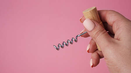 Female hand holding vintage corkscrew bottle opener over pink background with space for text