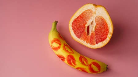Composition with fresh banana with traces of red lipstick and grapefruit on pink background. Sex concept