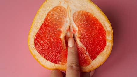 Vagina symbol. Fingers on grapefruit on pink background. Sex concept.