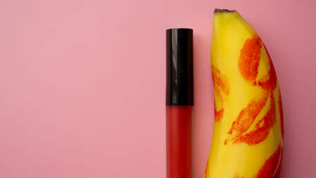 Red lipstick on a yellow banana on a pink background. Love and sex concept.