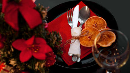 Setting for festive Christmas dinner on black table with New year decoration and dry oranges