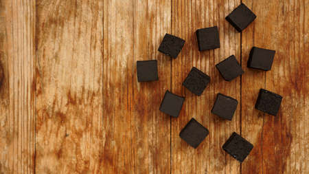 Cubes of coconut coal for hookah on wooden background. Top view, place for text
