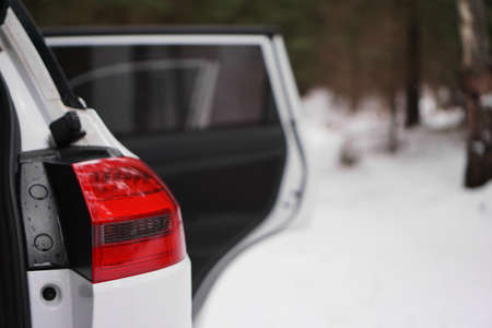 White car with red headlight and open door in winter forest