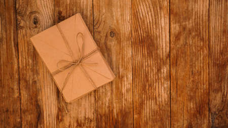 A lot of envelopes from kraft paper tied with string on a wooden background