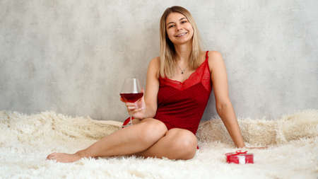 A beautiful young woman is sitting in red underwear on a white plaid with wine in her hand. Valentines day morning Stock Photo