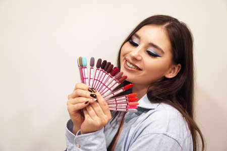 Pretty young woman smiling, holding a manicure and pedicure nail polish palette in a hand. Cosmetic products. Beauty salon.