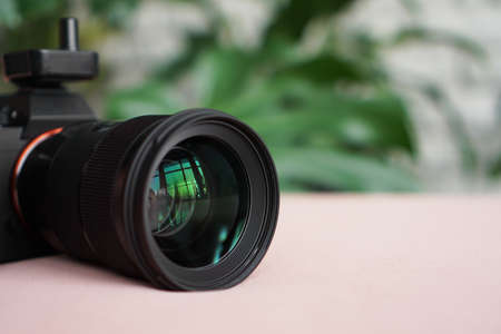 Black camera with a lens on a pink background and a blurred background of green leaves. No visible logos and brands. Focus on the lens
