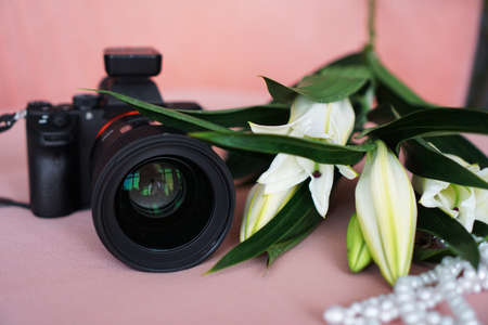 Black camera with a lens and white lilies and a necklace of pearls on a pink background. Selective focus. No visible logos and brands