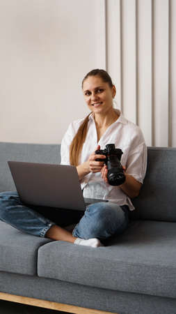 Happy young woman with photo camera using laptop at home. The photographer is holding the camera and smiling. Vertical photo.