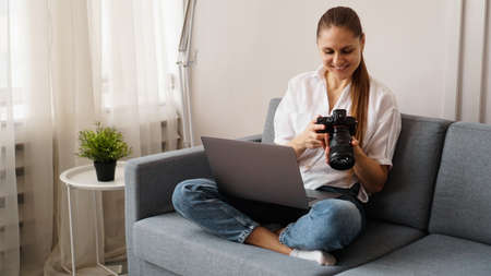 Happy young woman with photo camera using laptop at home. The photographer looks at the pictures taken and sits on the couch.