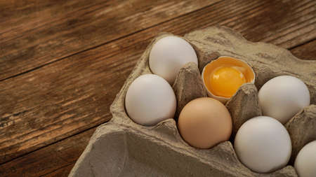 White eggs carton and cracked egg half with yolk top view on wooden background. Easter and healthy food breakfast cooking concept