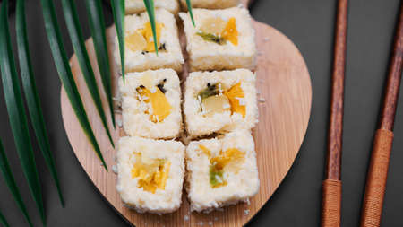 Dessert sushi. Sweet kiwi, pineapple sushi rolls. Sushi on a wooden tray on a black background with a tropical leaf