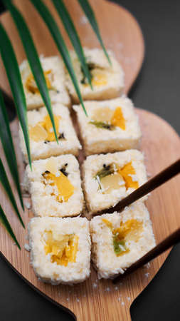 Dessert sushi. Sweet kiwi, pineapple sushi rolls. Sushi on a wooden tray on black background with tropical leaf. Vertical photo. Holding a sweet roll 免版税图像