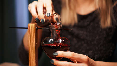 The woman witch prepares a potion. Red love potion in a heart-shaped glass jar. Love magic concept