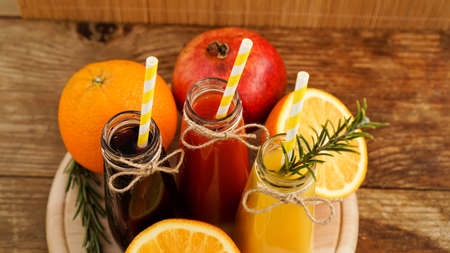 Home made lemonade in little bottles. Multicolored juices and fruits on wooden background. Paper straws in drinks.