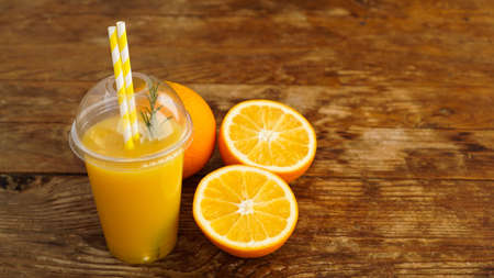 Orange juice in fast food closed cup with tubes on wooden table. Fresh summer drink. Photo for banner or advertisement of cafe and menu Stockfoto
