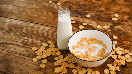 Healthy eating background. Fresh milk in bowl with cornflakes