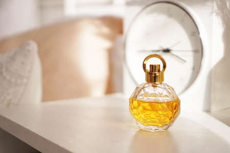 A bottle of yellow perfume on the night table