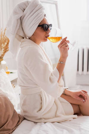Woman in a white bathrobe, towel and sunglasses. She is holding a glass of wine Фото со стока
