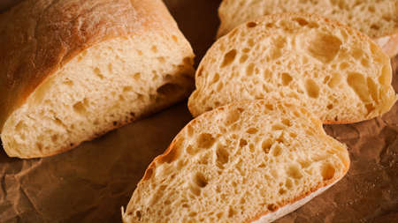 Ciabatta slices on craft paper. Fresh delicious pastries. Fresh homemade bread.
