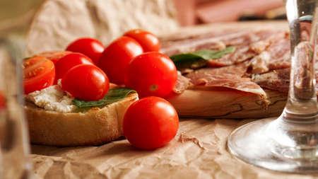 Bruschetta with cherry tomatoes. Wine glass, Italian appetizer.