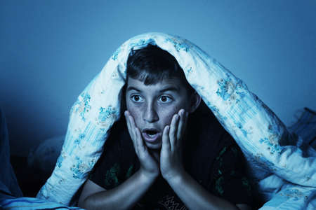 shoked: horrified boy watching film at night