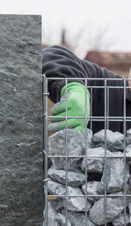 gabion mesh: filling the stone wall with gravel Stock Photo
