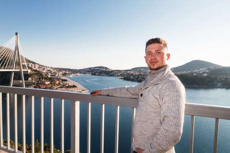 tourist stands in front of dubrovnik bridge photo