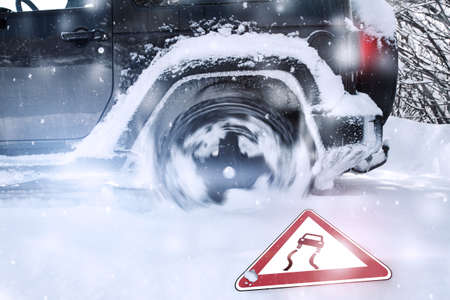 winter tires: Spinning Wheel of car tires at winter time in a snowy road with fall traffic sign Stock Photo