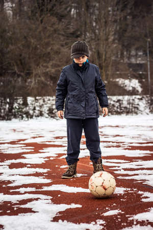 obesity kids: serious boy standing in front of ball
