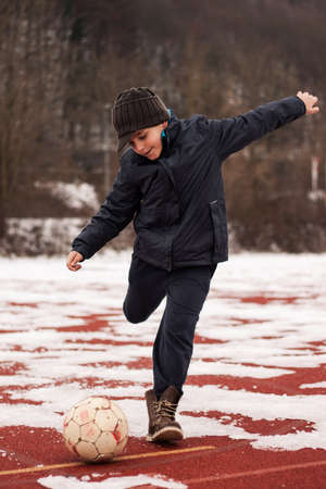 obesidad infantil: chico patear la pelota en invierno