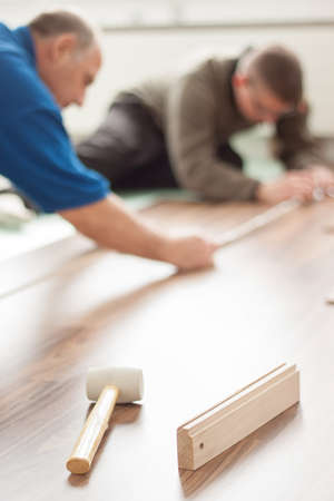 two handymen laying wooden laminate floor together photo