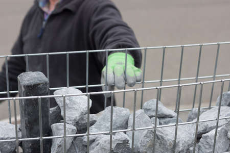 hand filling the stone wall mesh with granite stones Reklamní fotografie