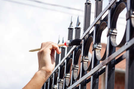 painting and decorating: hand with brush painting metal fence