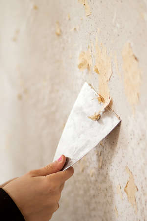 upholster: Remove wallpaper with spatula Stock Photo