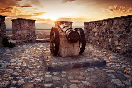old cannon at fortress in sunset light