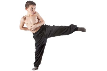 karate boy doing kick in front of white background