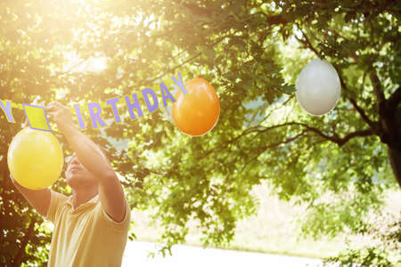garden parties: one hanging up balloons to preparing the birthday party Stock Photo
