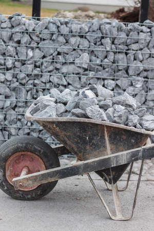 gabion mesh: wheelbarrow full with gravel
