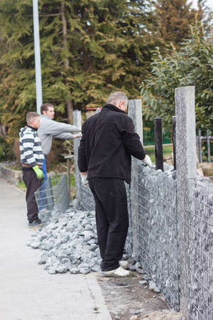gabion mesh: handymen working on nature stone gabion wall
