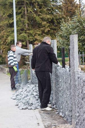 gabion: handymen working on nature stone gabion wall