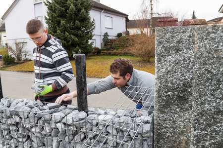 gabion: two worker filling the nature gabion stone with granite gravel