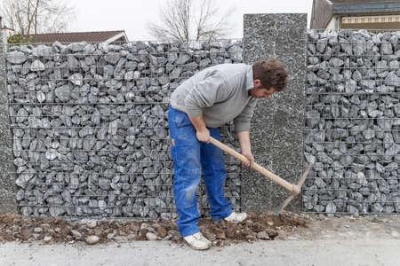 gabion mesh: Handyman working with hoe Stock Photo