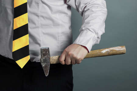 businessman with hammer in hand and working zone black and yellow stripes cravat photo