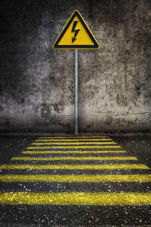 electricidad industrial: amarillo se�al de advertencia de la electricidad en la pared del grunge en frente de paso de peatones