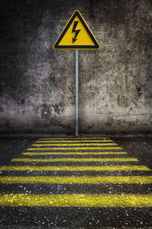 straight path: yellow electricity warning sign at grunge wall in front of pedestrian crossing